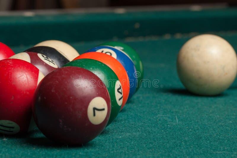 Billardkugeln und ein Stock auf einer grünen Tabelle Billardkugeln lokalisiert auf einem grünen Hintergrund lizenzfreie stockfotos