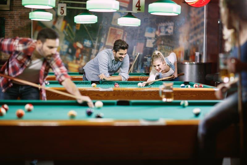 Billardspiele - Leute, die Pool zusammen spielend genießen lizenzfreie stockbilder