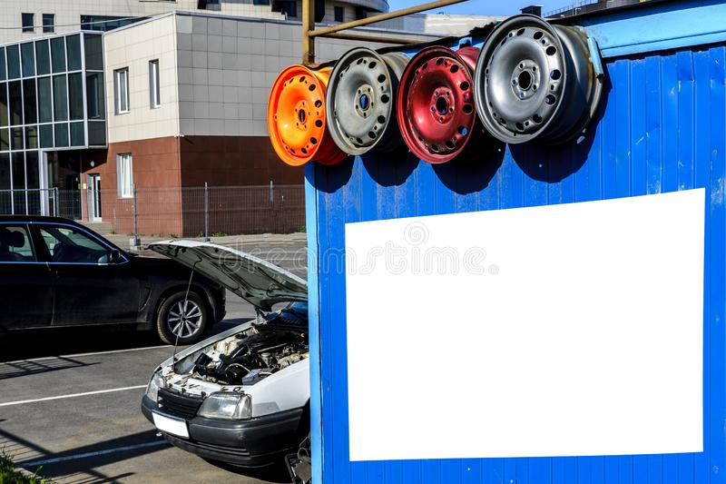 Billboard, small car center, service of cars and repair of disks on the street, wheels, the stock image