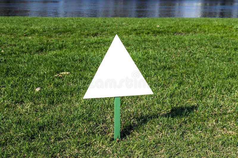 Billboard standing on the ground in the Park on the lawn, white advertising. Triangle royalty free stock image