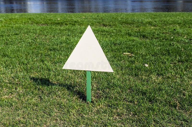 Billboard standing on the ground in the Park on the lawn, white advertising. Triangle stock photography