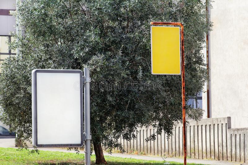 Billboard and yellow advert board in the street city, green plants, selective focus and closeup. Blank advertising display. royalty free stock images