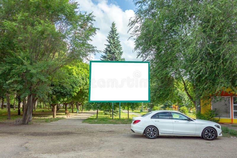 Billboard z kopii przestrzenią w parku Pusta plakat deska wśród zielonych drzew pod niebieskim niebem i Sztandaru panel z białym  zdjęcia stock