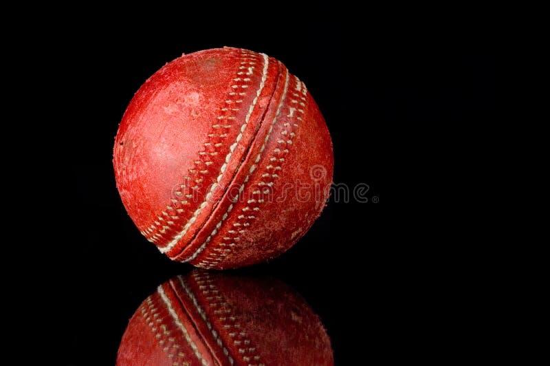 Bille de cricket rouge sur le fond noir image stock