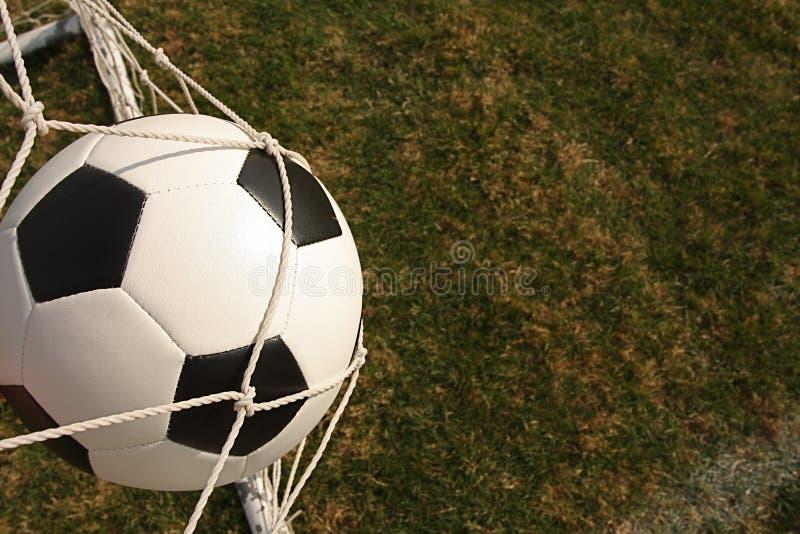 Bille de football dans le réseau de but photos stock