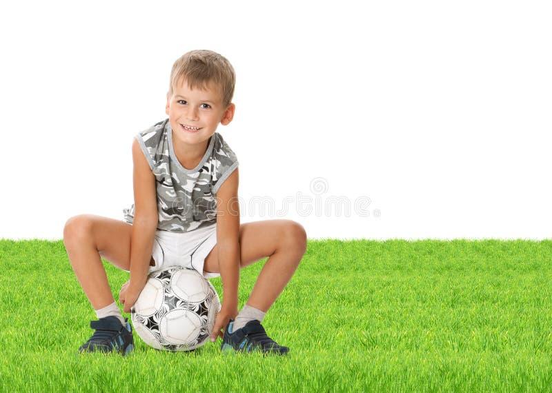 Bille de football de fixation de garçon photo stock