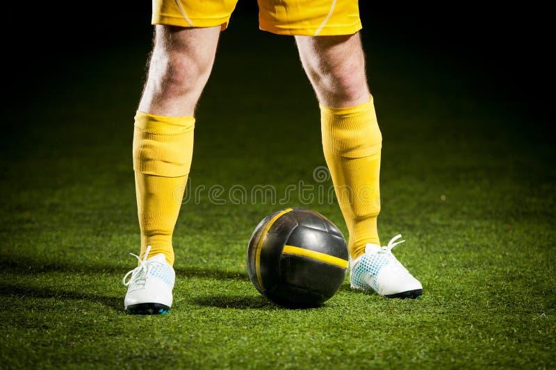 Bille de football et des pieds d'un footballeur images libres de droits