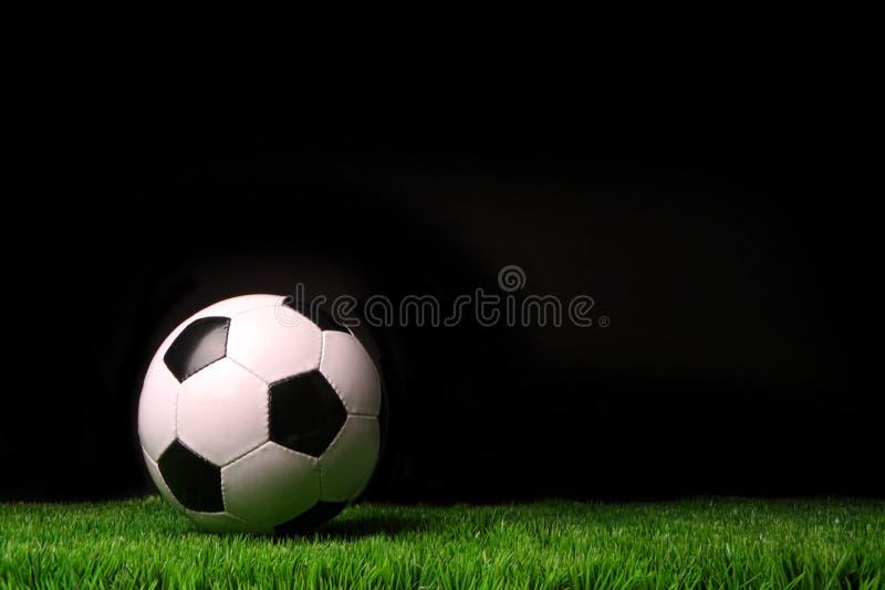 Bille de football sur l'herbe contre le noir photos stock