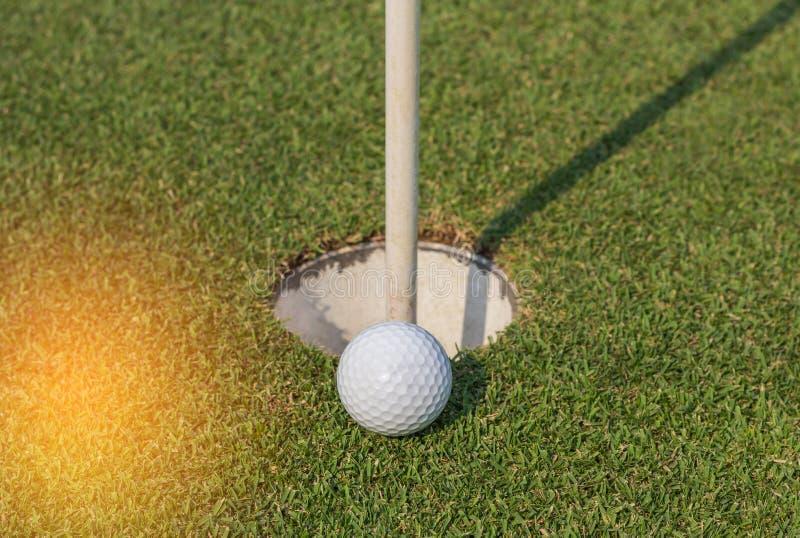 Bille de golf près du trou images stock
