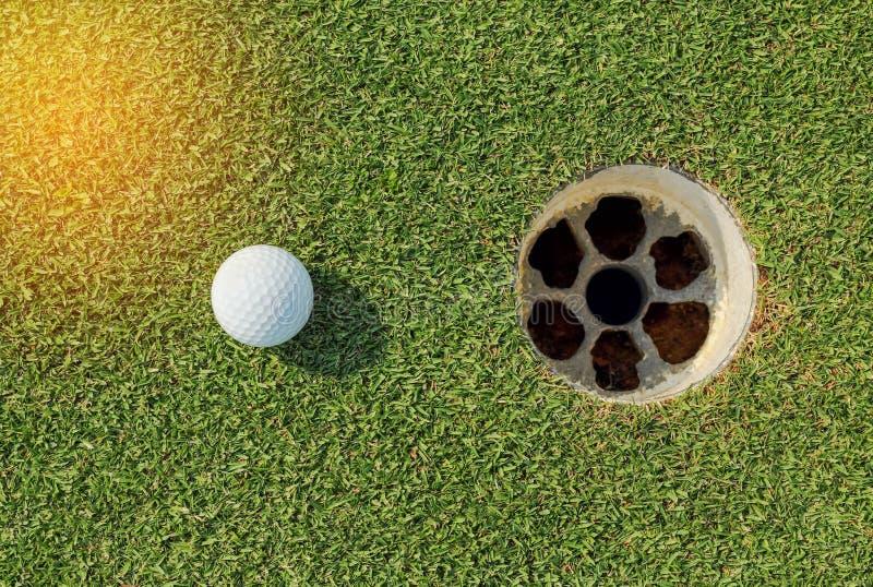 Bille de golf près du trou image libre de droits