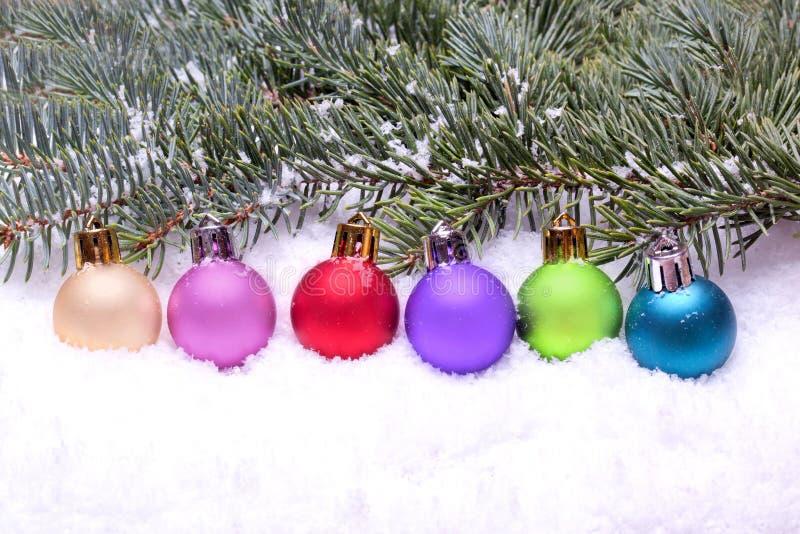 Billes colorées de Noël se trouvant sur la neige image libre de droits