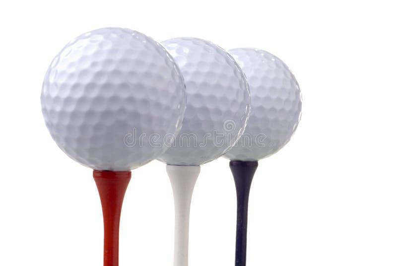 Billes de golf sur les tés rouges, blancs et bleus photographie stock