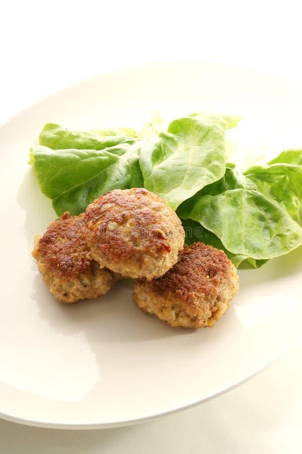 Billes de viande d'une plaque avec de la salade photo stock