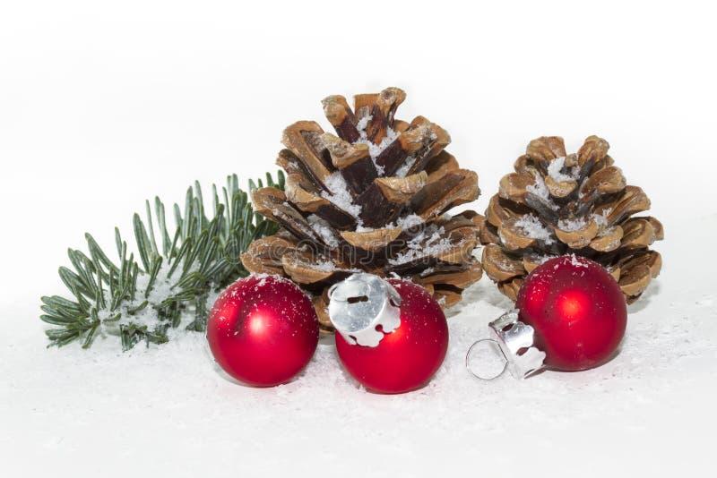 Billes rouges de Noël avec les pinecones et la neige images libres de droits