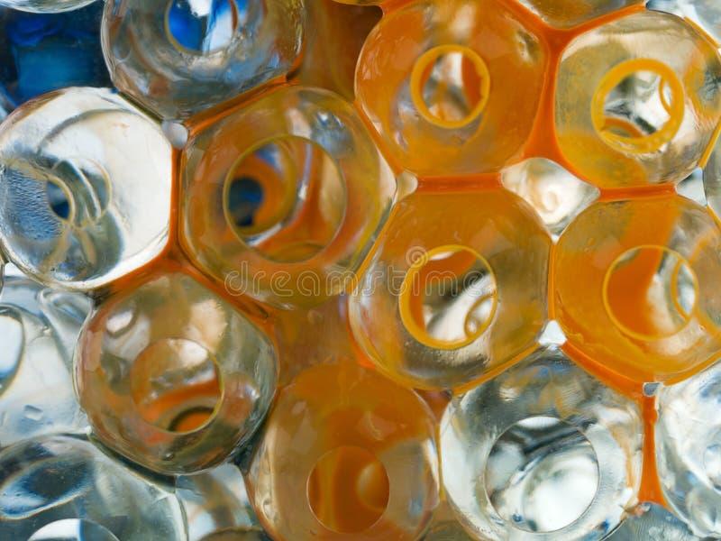 Billes transparentes avec l'encre bleue de colorant orange images stock