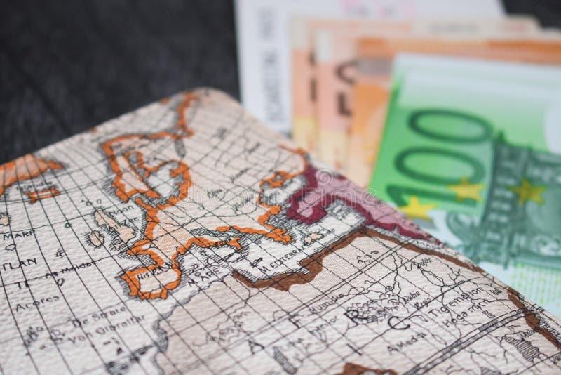 Billet d'argent, d'avion et carte Eurobanknotes avec la carte d'embarquement et la carte, sur le fond en bois noir photos libres de droits