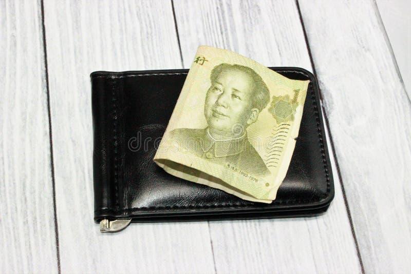 1 billet de banque chinois de yuans plié sur une bourse noire photographie stock libre de droits