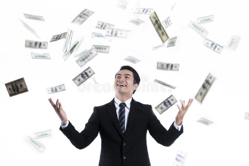 Billet de banque tombant au-dessus du jeune homme d'affaires photo libre de droits