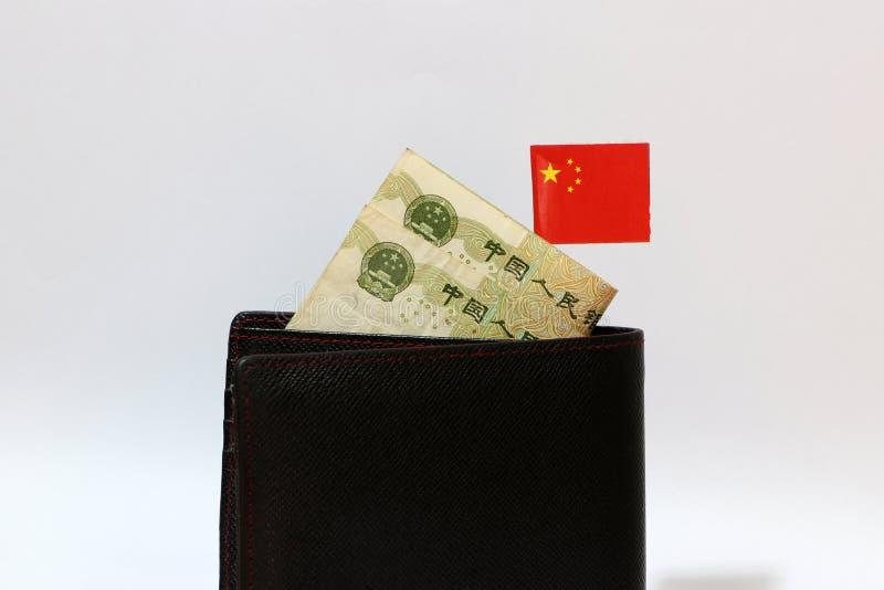 Billet de banque de yuans de la Chine et de mini bâton de drapeau de nation chinoise sur le portefeuille noir avec le fond blanc images libres de droits