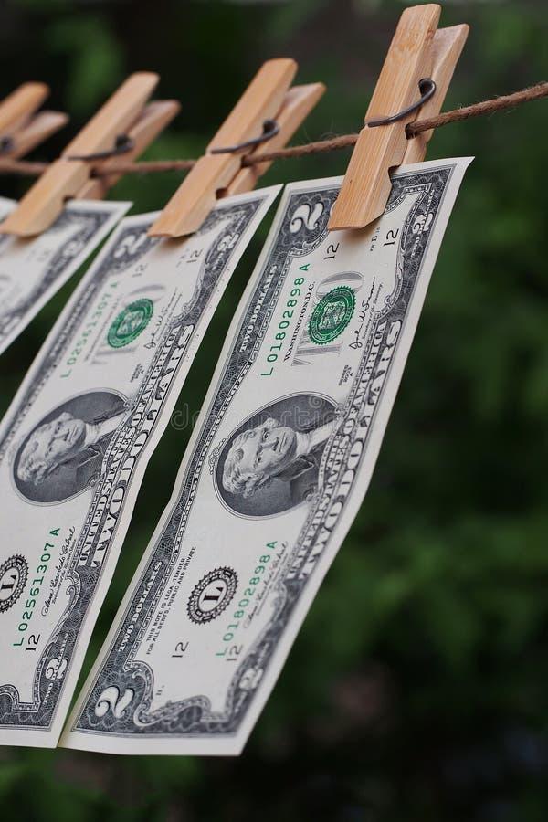 Billet de deux dollars fixe sur la pince à linge avec le backgroung vert de tache floue photographie stock