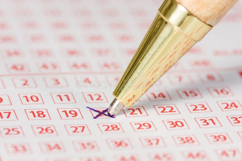 Billet de loterie avec un nombre marqué et un stylo images stock