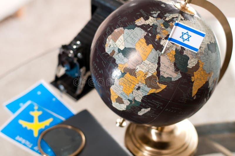 Billete de avión y bandera israelí en el globo imagenes de archivo