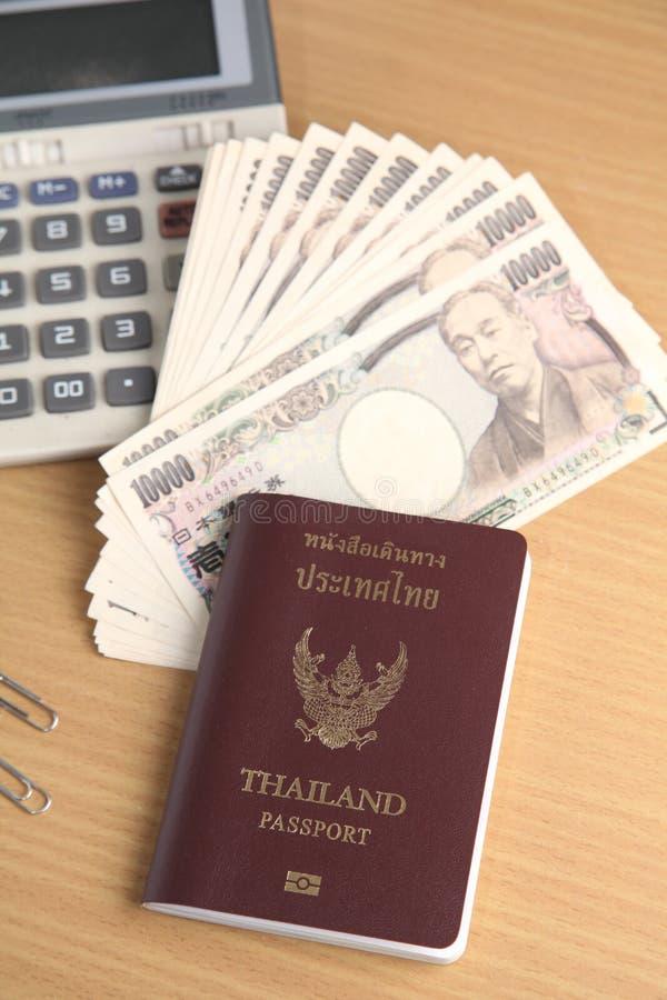 Billete de banco de los yenes japoneses y calculadora tailandesa del pasaporte foto de archivo libre de regalías