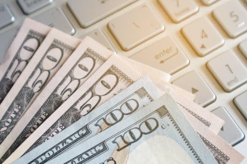 Billete de banco del dólar en un ordenador portátil Dinero ganado trabajando del ordenador portátil en casa Trabajo independiente foto de archivo