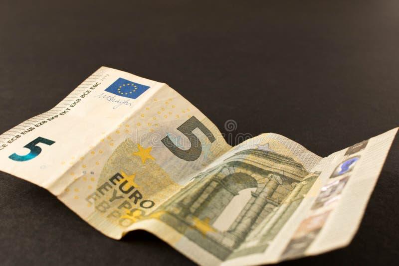 Billete de banco del euro 5 en un fondo oscuro Cierre para arriba El concepto de ahorros fotografía de archivo