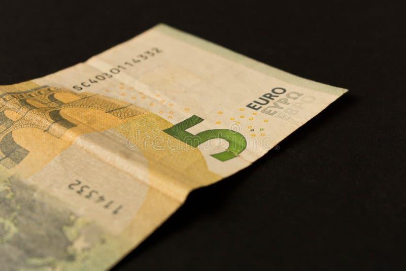 Billete de banco del euro 5 en un fondo oscuro Cierre para arriba El concepto de ahorros fotografía de archivo libre de regalías