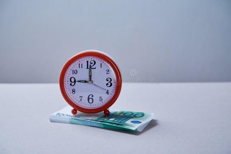 Billete de banco euro con el reloj en la composición gris del fondo Concepto para el dinero o el crédito bancario del tiempo fotografía de archivo