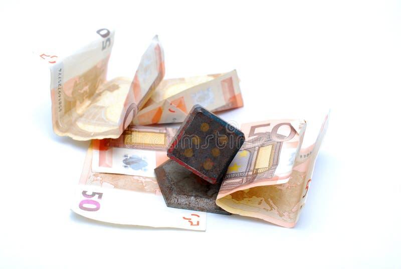 billete de banco euro presionado por el recuerdo del vintage, dado de juego del metal oxidado pesado foto de archivo