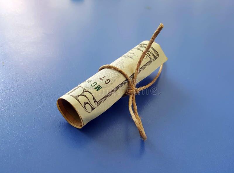 billete de banco rodado del dólar en un fondo azul imágenes de archivo libres de regalías