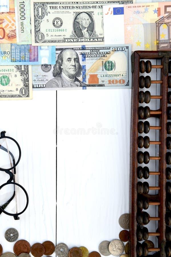 Billete de banco y moneda con los vidrios foto de archivo