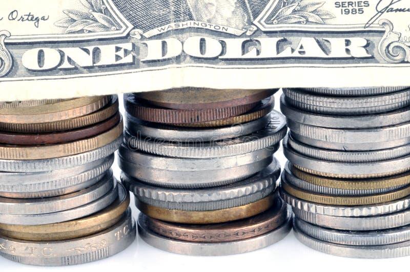 Billete de dólar en pilas de monedas fotos de archivo libres de regalías