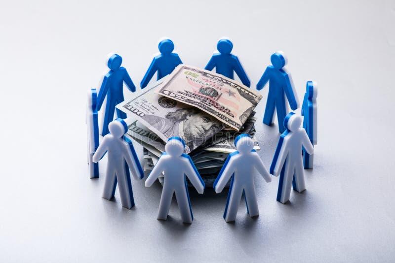 Billetes de banco apilados rodeados por las figuras humanas imagen de archivo libre de regalías