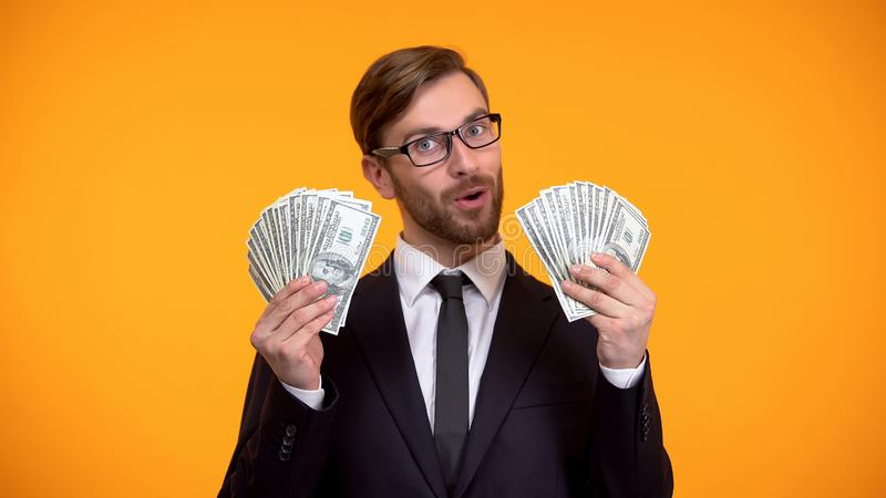 Billetes de banco confiados del d?lar de la demostraci?n del hombre de negocios, trabajo bien pagado, honorarios del efectivo imagen de archivo