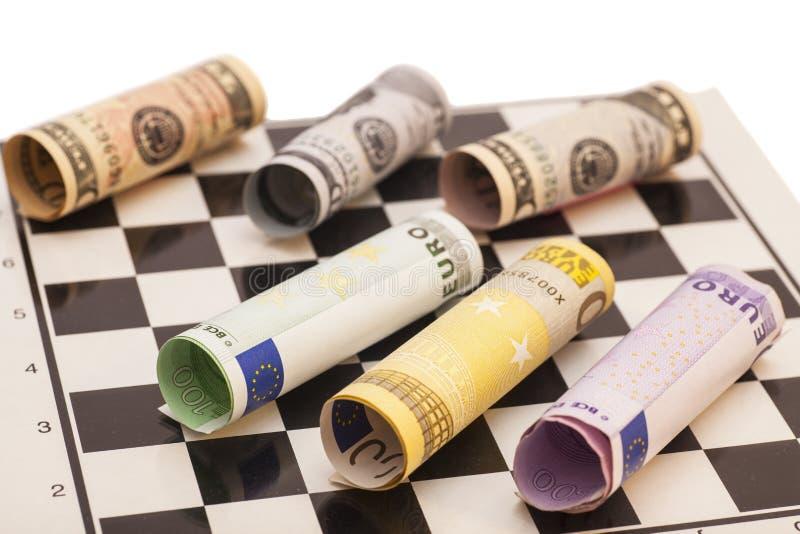 Billetes de banco de los dólares y del euro en tablero de ajedrez fotografía de archivo