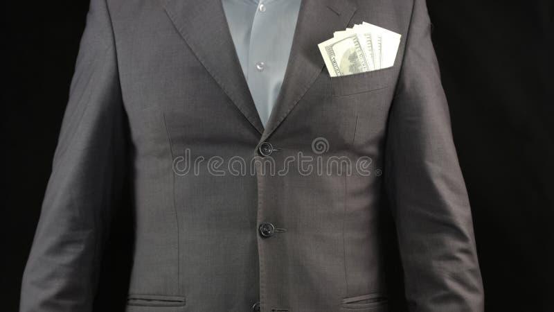 Billetes de banco del dólar en el bolsillo del hombre de negocios, los ahorros y la renta, estrategia del éxito imagen de archivo