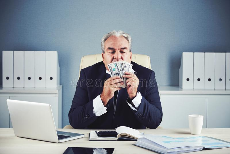 Billetes de banco del dólar del hombre de negocios que se besan maduro acertado foto de archivo