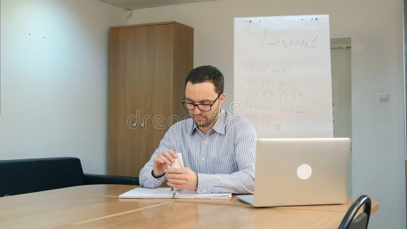 Billetes de banco del dólar de la cuenta del profesor de sexo masculino que se sientan en el escritorio en sitio de clase imagen de archivo libre de regalías