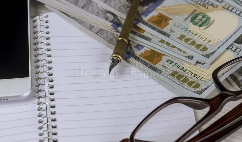 Billetes de banco del d?lar, mentira del primer en una hoja de papel blanca al lado de una pluma y vidrios en un marco pl?stico foto de archivo