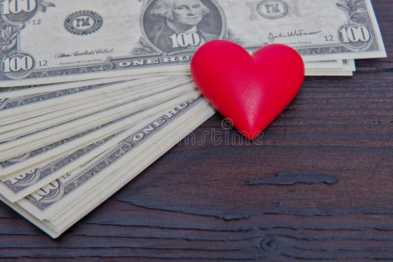 Billetes de banco del dólar y corazón rojo en una tabla fotos de archivo libres de regalías