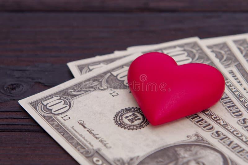 Billetes de banco del dólar y corazón rojo en una tabla foto de archivo libre de regalías