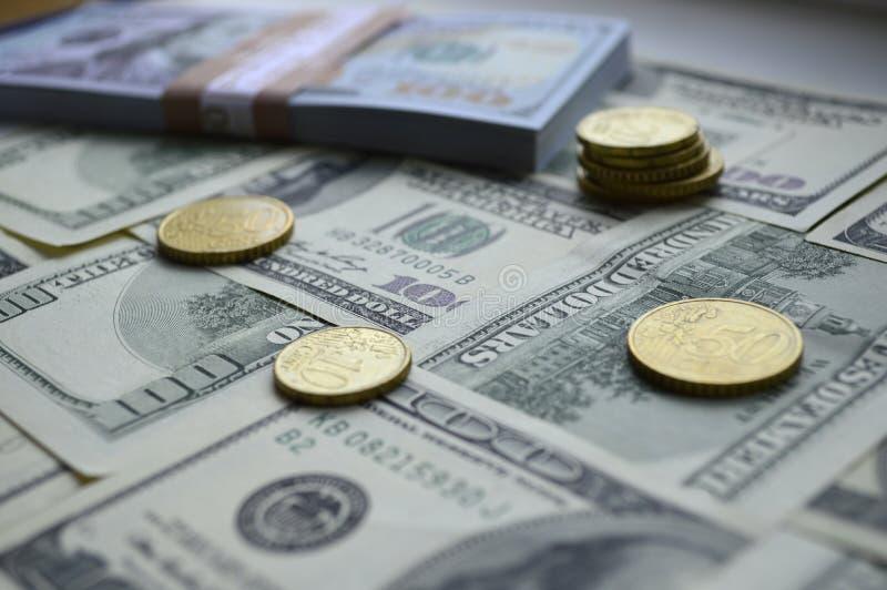 Billetes de banco dispersados de 100 dólares de EE. UU. y monedas del euro fotos de archivo libres de regalías