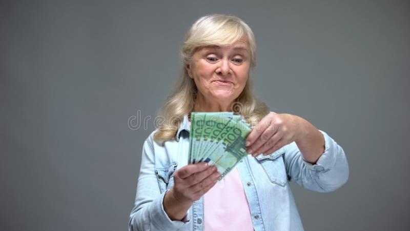 Billetes de banco euro de cuenta femeninos mayores alegres, compras de planificación, servicio de préstamo imágenes de archivo libres de regalías