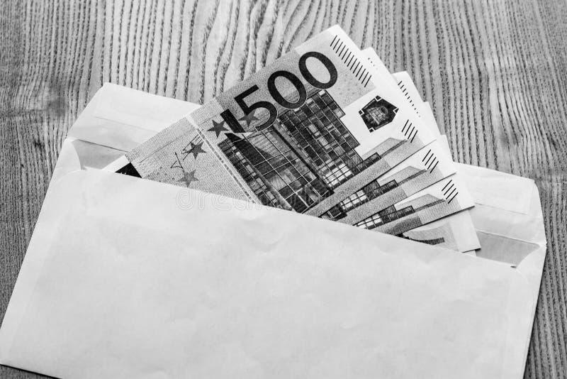Billetes de banco euro en un sobre blanco en un fondo de madera en color blanco y negro foto de archivo libre de regalías