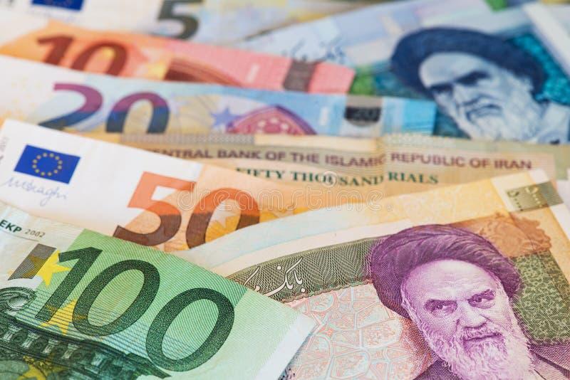 Billetes de banco euro de la moneda y billetes de banco de la moneda del rial iraní cercanos encima de imagen imágenes de archivo libres de regalías