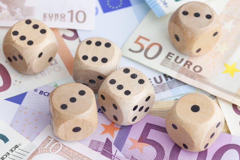 Billetes de banco euro y dados de madera en ellos foto de archivo