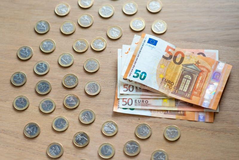 50 billetes de banco euro y monedas de 1 euro en un fondo de madera ligero imágenes de archivo libres de regalías